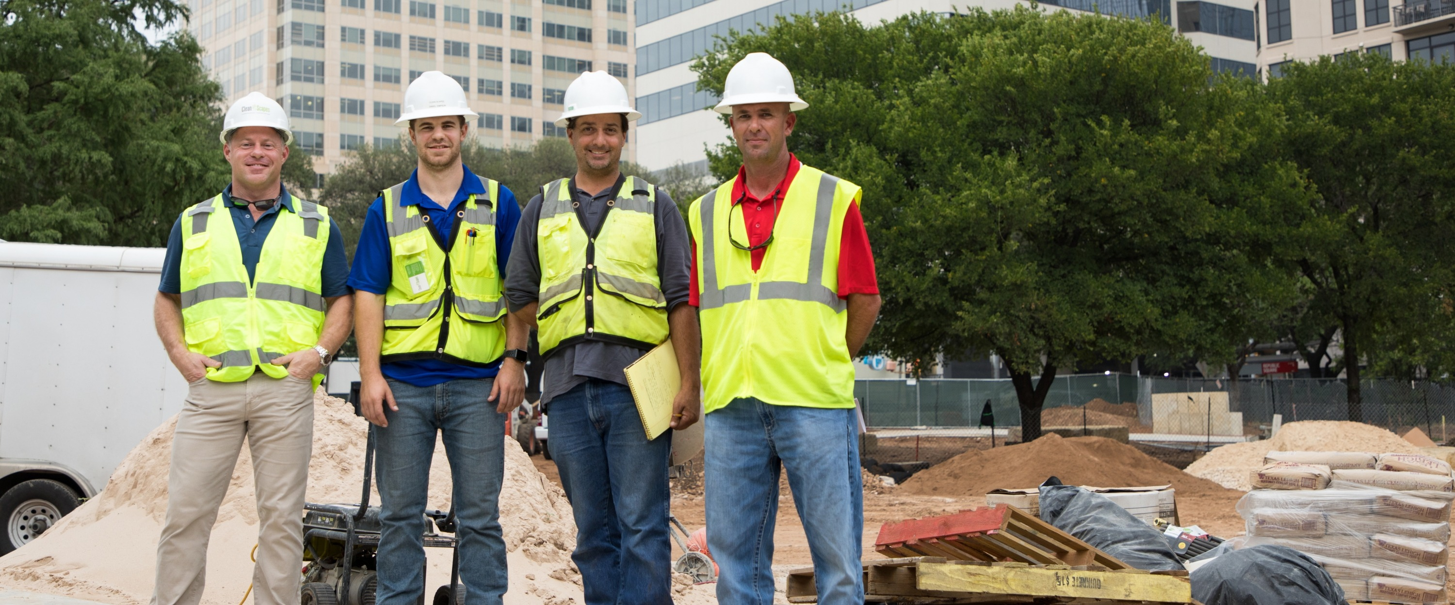 Members of Clean Scapes posing in front of the construction of Republic Square Park
